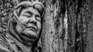 Rosalyne Mathias, 60, crushed by emotions, takes a moment to hug the tree that grew at the exact spot where she had a miscarriage, 43 years ago, after having made a circle of cedar leafs around the tree. After many sexual agression between age 15 to 17, she got pregnant. 43 years later, she return on the site with the hope to find peace. Addressing to her lost child … and to her lost childhood.